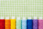 Row of colorful thread spools — Stock Photo