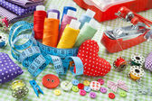 Spools of colorful thread, buttons, fabrics, measuring tape, pin — Stock Photo