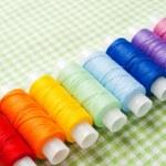 Row of thread spools in rainbow colors — Stock Photo