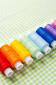 Row of thread spools in rainbow colors — Stockfoto