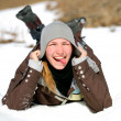 Close-up portrait of smiling young woman lying on a snow indicat — Stock Photo #46253013