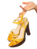 Close up portrait of a female hand holding yellow shoe , isolate — Stock Photo