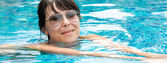 Beautiful young girl in sunglasses floating in the pool — Stock Photo