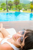 Close-up portrait of young smiling woman with a sunglasses lying — Stock Photo