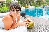 Close-up portrait young pretty woman drinking coconut cocktail  — Stockfoto