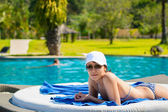 Portrait of a young beautiful woman in white cap and sunglasses  — Stock Photo