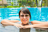 Portrait of a beautiful young woman in sunglasses in the pool — Stock Photo
