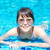 Portrait of a beautiful young girl in sunglasses floating in the — Stock Photo