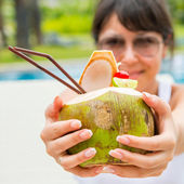 Young pretty woman with a coconut cocktail — Stock Photo