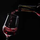 Red wine pouring into wine glass isolated on black — Stock Photo