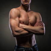 Muscular naked man on black — Stock Photo