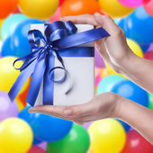 Hands holding gift in package with blue ribbon — Stock Photo