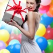 Stock Photo: Young smiling woman holding gift