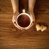Woman holding hot cup of tea with cookies on wooden table — Stock Photo