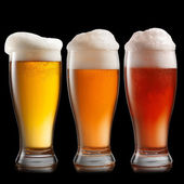 Different beer in glasses isolated on black background — Stock Photo