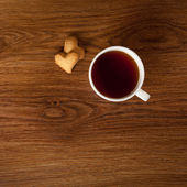 Hot cup of tea with cookies on wooden table — Stock Photo