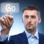 Business man pressing Go button on touchscreen — Stock Photo