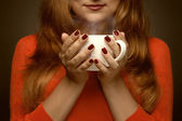 Woman holding hot cup and smiles — Stock Photo