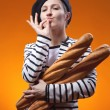 Woman holding baguettes and shows that taste is delicious — Stock Photo #39117485