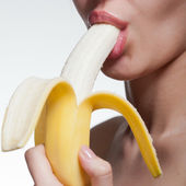 Young woman biting banana isolated on white — Stock Photo