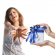 A girl reaching out for men's hands holding a present on white b — Photo