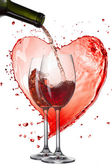 Red wine pouring into glasses with splash against heart isolated — Stok fotoğraf