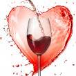 Stock Photo: Red wine pouring into glass with splash against heart isolated o