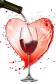 Red wine pouring into glass with splash against heart isolated o — Stock fotografie