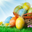 Color easter eggs in basket against blue sky and clouds — Stock Photo #41265601