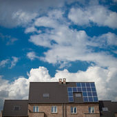 New houses with solar panels on roof under blue sky and clouds — Stock Photo