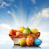 color easter eggs in basket against blue sky and clouds — Stock Photo