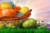 color easter eggs in basket against sky and clouds — Stock Photo