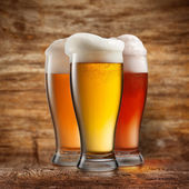 Different beer in glasses on wooden background — Stock Photo