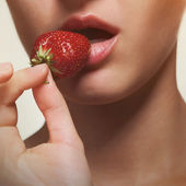 Young woman biting strawberry isolated on white — Stock Photo