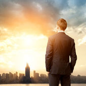Business man look sunrise in the city — Stock Photo