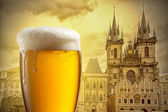 Glass of beer against Tyn Church in Prague — Stock Photo