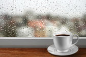 Coffee cup against window with rainy day view — Stock Photo
