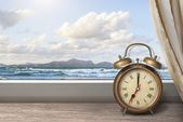 View of summer sea under blue sky from window with alarm clock — Stock Photo