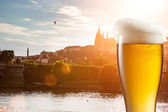 Glass of beer against view of the St. Vitus Cathedral in Prague — Stock Photo