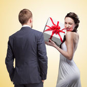 Man looking on smiling woman holding gift — Stock Photo