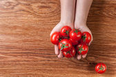 Red tomatoes in hands on wood — Stock Photo