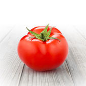 Red tomato isolated on wood — Stock Photo