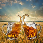 Splash of beer against wheat and sunset — Stock Photo