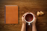 Woman with cup of tea, cookies and book — Stock Photo