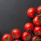 Red tomatoes on blac — Stock Photo