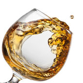 Splash of cognac in glass isolated — Stock Photo