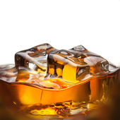 Splash of whiskey with ice in glass isolated on white — Stock Photo
