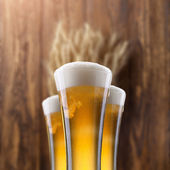 Glass of beer with wheat on wood — Stockfoto
