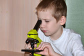 The boy looks in a microscope — Stock fotografie
