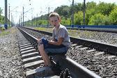 Portret nastoletni chłopak siedzący na szynach — Zdjęcie stockowe